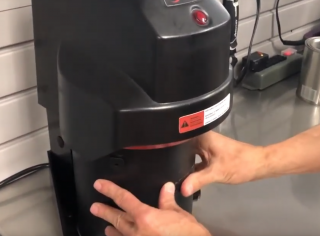 A man using the RADIA Auto Lid Press to seal a can of paint with a YouTube play button overlaid